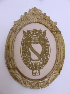 Stemma araldico monocromatico oro in cornice artigianale.