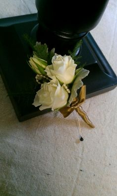 White spray rose boutonniere with old- gold ribbon and pearls
