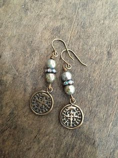 These beautiful earrings feature sea green patinaed Czech beads, aged crystals and rustic bronze Saint Benedict coins.