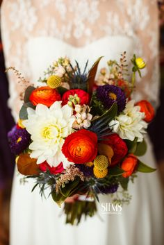 Naturally shaped bouquet of orange ranunculus, yellow spray roses, reddish-pink spray roses, seeded eucalyptus, magnolia leaves, pale pink astilbe, peach stock flowers, blue thistles, purple asters, white dahlias, and red garden roses wrapped in ivory ribbon with the stems showing.  www.stemfloral.com  |  www.jakeholt.com