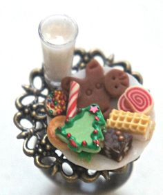 This ring features a plate of handmade Christmas cookies sculpted from polymer clay along with a miniature glass of milk. The minis are attached to an adjustable antiqued bronze ring that fits most ri