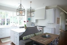 A pair of iron and glass lanterns hang over a kitchen island fitted with a gray banquette lined with yellow and gray bolster pillows facing a reclaimed wood top dining table lined with Ghost Chairs.