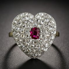 This romantic and ravishing heart shaped ruby and diamond ring, dating  from the turn-of-the-last-century, is tightly paved with fine, bright-white, high-domed rose-cut diamonds of a quality we rarely see. The gently puffed heart is crafted in platinum over gold and is centered with a gorgeous rich red oval ruby. A truly exquisite original Edwardian sparkler in a ring size 7 3/4. The heart measures 3/4 of an inch in both directions.