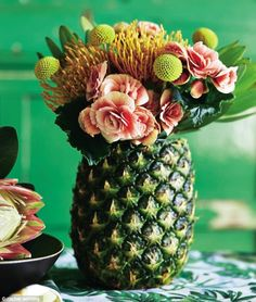 FEELING FRUITY? For a fun centrepiece, turn a pineapple into a fabulous vase. Chop the crown leaves off a large pineapple and remove the flesh from inside. When it is hollowed out, you can either fill it with water – test for leaks first – or fill a glass or small vase and place it, unseen, inside the pineapple. Arrange a selection of tropical flowers and greenery such as coral begonias, yellow billy buttons (craspedia), leucospermum tango and protea in the pineapple vase.