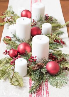 Christmas centerpiece with faux greenery, white candles, red berries and red Christmas tree ornaments #christmasdecor #centerpiece #decoratingachristmastree #christmastreeornaments