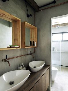 The exposed copper of the pipes and the wood-framed mirrors give a raw and natural feel to the master bathroom