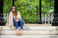Young beautiful woman sitting on the stairs in the park