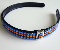 Flexible, black plastic headband featuring sun and sapphire crystals.