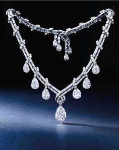Fine Diamond Necklace, Bulgari, Circa 1950s:  Of ribbon scroll motif, suspending to the front with a pear-shaped diamond weighing 7.04 carats, decorated by six similarly-cut diamonds, to a necklace set with brilliant-cut and baguette diamonds terminating on a clasp highlighted by four pear-shaped diamonds, the diamonds together weighing approximately 52.50 carats, mounted in platinum, length approximately 360mm, signed.