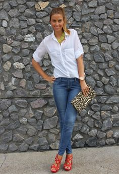 White Blouse, ponytail, jeans, red sandal heels, statement necklace and a leopard accessory. Or it could be a white tank top instead