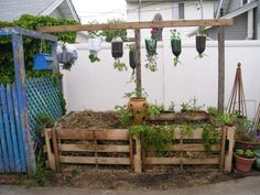 Pallet composter & pallet potato bin IN USE! Check out the recycled bottles as topsyturvy planters.