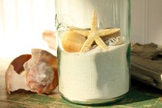 do this with our sand from jamaica and seashells to display! starfish, shells, and sand in a bottle on table