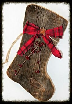 Our primitive barnboard Santa boots are adorned with red Christmas homespun, red pip berries, and a rusty star. Perfect for any primitive Christmas decor.