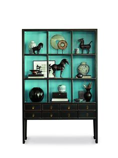 The imported piece, which is exclusive to Gump's, is constructed from select Asian hardwood and features a black lacquered finish that undergoes an edge-rubbing process to allow warm tobacco hints to emerge.  A pale blue background sits behind three open shelves, and eight dovetailed drawers feature decorative antique brass and half-round molding.
