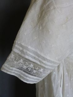 Scottish Embroidered Gown c. 1805. the fine muslin sprinkled with minute embroidered chain stitch squiggles, leaves and flowers worked in white cotton with a tambour hook, the bodice with scoop neck, linen lined bodice and original ties to the front, short slightly shaped sleeves, their edges with Buckingham lace insert between shallow flat tucks, the back with deeply inset sleeves, the fall front with similar lace curving inserts and vertical fine tucks, the apron skirt gathered with…