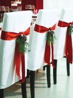 Christmas Table Ideas Using Red and White: Give your dining room chairs a festive touch by wrapping them with wide red satin ribbon and adding some greenery.: