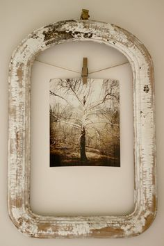 hang an old photograph with a clothes pin in a shabby frame.