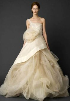 Vera Wang  (2012) - Frothy ivory confection.  Tulle gown with organza handkerchief overskirt.  Bodice is strapless except for single asymmetrical spaghetti strap.  Large tulle bloom on the hip