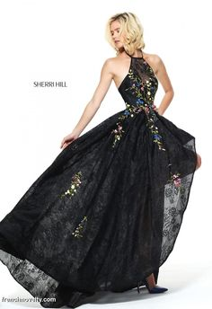 Sherri Hill 50967 is a high low prom gown with a colorful floral design and a spaghetti strap halter top.