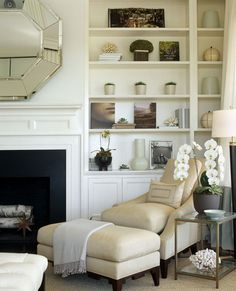 Eileen Marcuvitz of Plum Interiors....shelf styling as well as the comfy chair and ottoman at an angle near the fireplace and table styling.