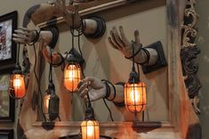 Dollar store hands painted & mounted to a picture frame.  Wrap corded lanterns around hands. This version is electric,  but for a less involved prep, use old candle lanterns with battery operated candles.