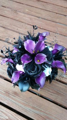 Black and purple bouquet, Calla lilly, roses, feathers. Stunning bouquet for my black and purple nightmare before Christmas wedding. In love with this arrangement                                                                                                                                                                                  More