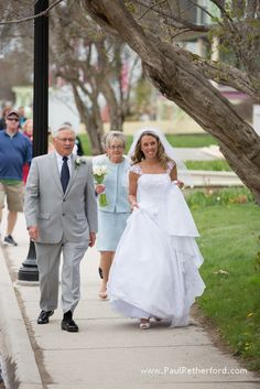 Not many Brides walk to their Wedding!  Mackinac Island is one place that I see this happen often since Wedding venues are so close at times.  Photo by Paul Retherford, http://www.PaulRetherford.com ~ flowers by St. Ignace Greenhouse