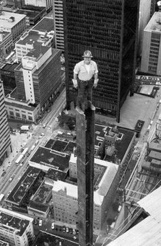 Construction worker atop a very tall structure with no safety harness