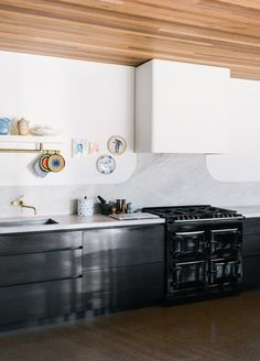 Melbourne home belonging to artist Anna Charlesworth, her real estate agent husband Peter Stephens, and their 12 year old daughter Nina. Photography by Brooke Holm, production by Lucy Feagins / via The Design Files. Aga Stove, Kitchen Stove, Timber Kitchen, Warm Kitchen, Kitchen Cabinets, Home Decor Kitchen, Kitchen Interior, Kitchen Design, Kitchen Ideas