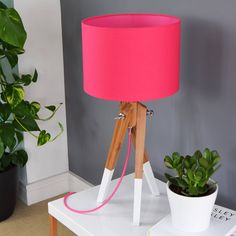 One of our Cerise pick and mix lampshades with a matching pink lining on our bamboo and white dipped leg table lamp base.
