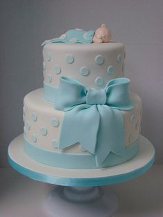 2 tier cake with baby blue polka dots and bow. It is simple, classic and sweet with a baby boy sleeping on top.