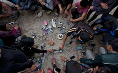 Nepalese villagers charge their cell phones in an open area in Kathmandu, Nepal