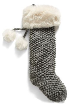 Add a rustic, cozy-chic touch to the holiday décor with this chunky knit stocking featuring lavish faux-fur trim and pompom embellishments.