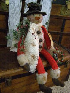 Prim snowman in old red quilt.