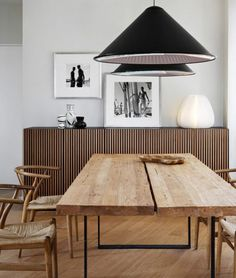 example of a reclaimed wood table with danish modern chairs. The pops of black ground the space. White wall keeps it modern.