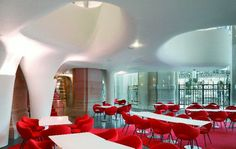 L'Opera Restaurant in Paris by Odile Decq, with white sculpted ceiling, glass walls, white tables, and red Eames chairs.