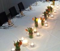 Large table centrepiece / table-scape. Orange tulips, jars, twine, plenty of t light candles. Place cards were brown paper bags full of Haighs Chocolate.  mmmm