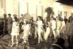 """TEATRO ANDANTE  O grupo """"Peregrinos Andantes Errantes"""" é formado por alunos do curso de teatro da Casa da Cultura Paraty Cultural, que decidiram, além das aulas normais, se unir ao grupo de teatro dirigido por Silvina Hurtado, professora da Casa.  No dia 16 de junho, junto com o grupo Olho Negro, os alunos fizeram uma performance desde as ruas do Centro Histórico, até o pátio da Casa, chamando o público para abertura da exposição """"Pequenas Miscelâneas (de caixote)"""", de Renata del Campo.  A…"""
