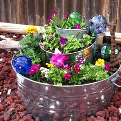 Container flower garden Stack metal containers with soil.  Plant flowers and add accent pieces!