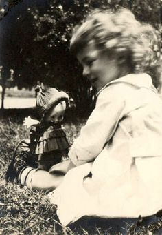 antique photograph of a child playing with a kewpie doll.