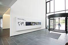 Blickfang im Eingangbereich des Hörmann Forums: Videowall der komma,tec redaction, die in ein hinterleuchtetes Poster integriert wurde. (Digital Signage)
