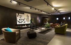 Com iluminação de spots, o espaço criado pelo arquiteto João Armentano é intimista e moderno. Os quadros apoiados na prateleira são uma ótima ideia para copiar