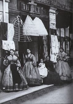"Ca.1860, and NOT by Eugene Atget. This has been passed around labelled ""The Crinoline Shop, by Eugéne Atge, 1880,"" but that is obviously wrong. Eugéne Atget (note the final T) was born in 1857 and did not start taking photographs until the late 1880s, nor his famous street scenes until the end of the century. This image is clearly between 1860 and 1864 by the fashions - but it does appear to be French."