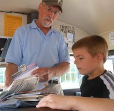 Southern Door bus driver Ted Chaudoir shows first-grade student Randon McLeod a selection of books as he boards the bus. #pbis