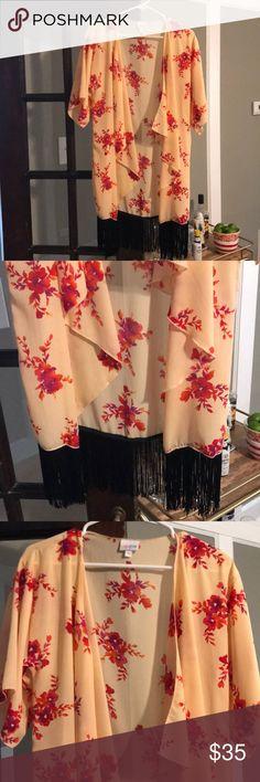 NWOT LuLaRoe Monroe kimono NWOT LuLaRoe Monroe kimono. Size small, never worn. Peach with orange/pink/purple floral pattern and black fringe. LuLaRoe Tops
