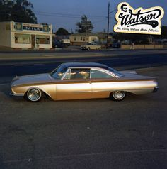 A really great early evening photo of a really great 1960 Ford Starliner Custom in the front of Larry Watson's shop everything on it is just so right. The colors which appear to be dark champaign pearl with a dark candy brown on the top. But this is hard to tell in the late eventing sunlight. The stance on this car is really working well for it making it look like its going fast standing still.