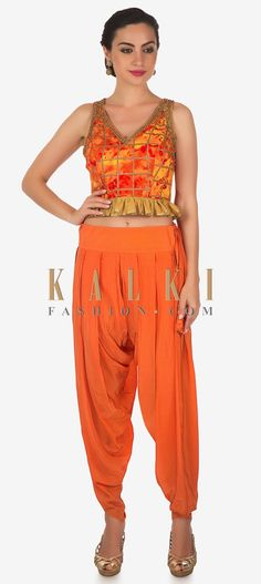 Orange pants featuring in crepe satin. Matched with crop top in with frills at waist line. Neckline is embellished in kundan embroidery. Orange Pants, No Frills, Parachute Pants, Neckline, Satin, Queen, Trends, Crop Tops, Embroidery