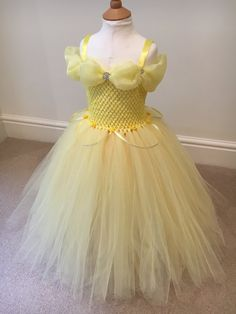 Beautiful Belle Inspired Tutu Dress   Handcrafted from layers of contrasting yellow ( Nylon ) tulle. with Organza billows around the shoulders and a long Organza sash at the back. Detailed with Rhinestone buttons at the front and a handmade chiffon rose between the shoulders. Your little princes will charm any Beast whirling and twirling the hours away in this fabulous design.   She will truly be the Belle of the ball.