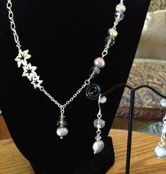 Pretty asymmetrical necklace with a floral station, potato pearls & Swarovski crystals! So unique...