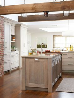 Exposed brick, white cabinets, and a gorgeous kitchen island— what's not to love about this kitchen? More univerrsal kitchen design ideas: http://www.bhg.com/kitchen/remodeling/planning/universal-kitchen-design-ideas/?socsrc=bhgpin100113woodbeams&page=1